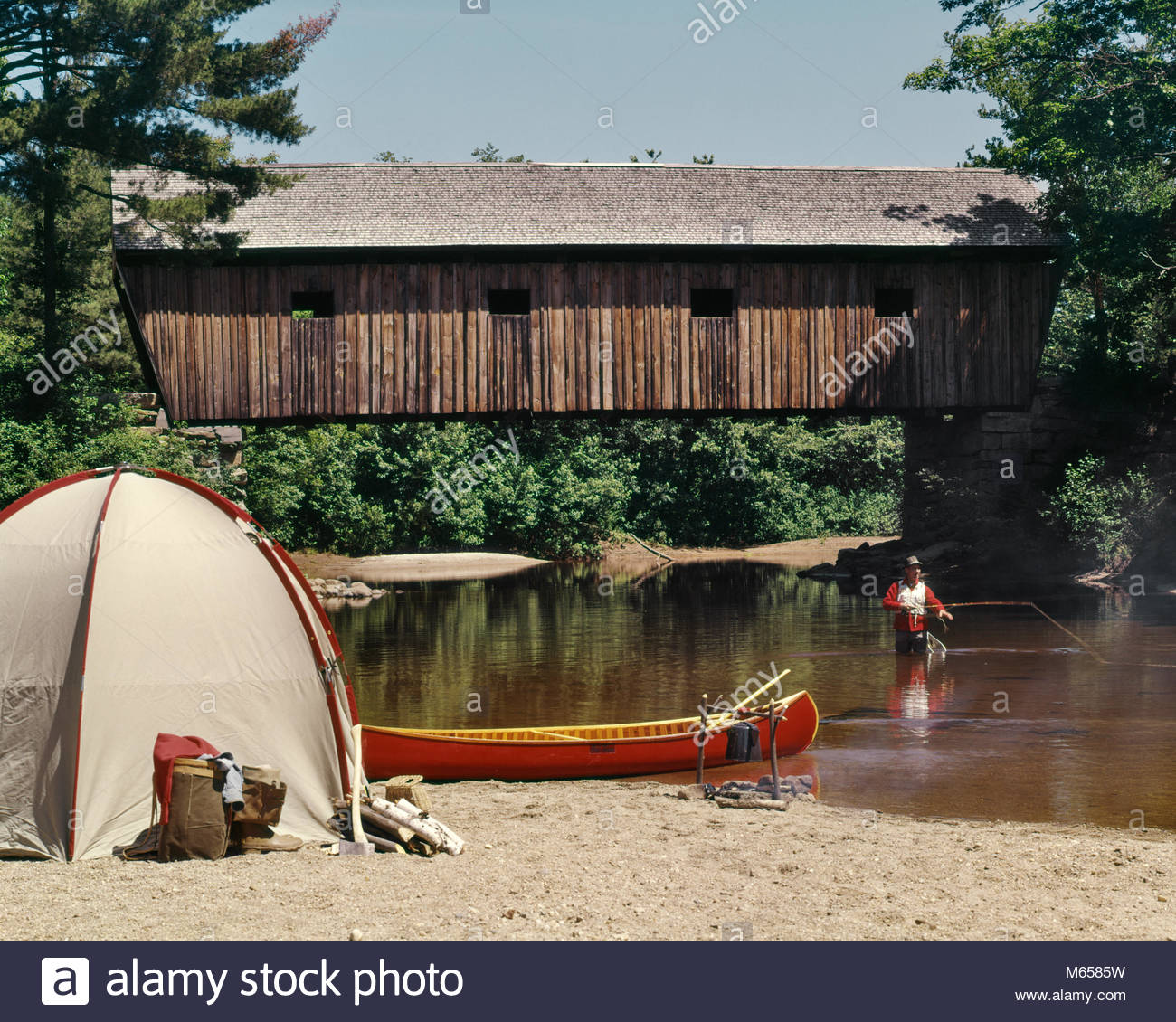 1960s MAN STANDING IN STREAM FLY FISHING BESIDE CAMPSITE TENT 1300x1130