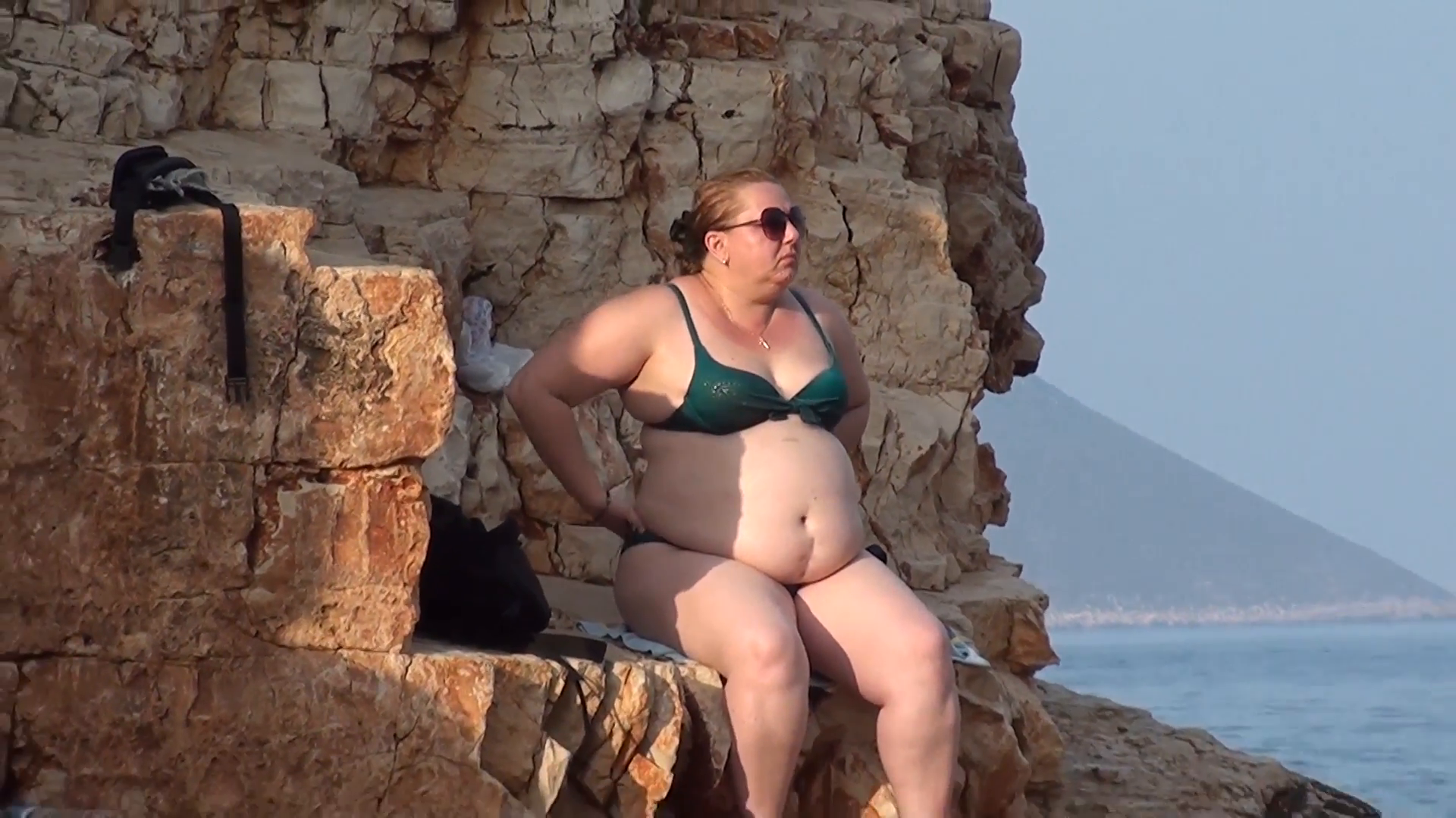 Fat woman in bathing suit sits on rock at the natural beach zoom 1920x1080