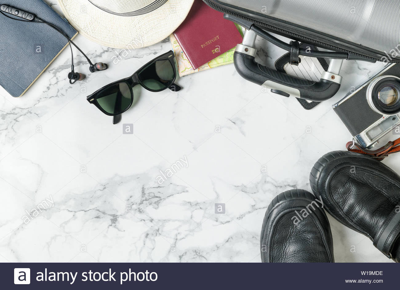 prepare suitcase accessories and travel items background on marble 1300x943