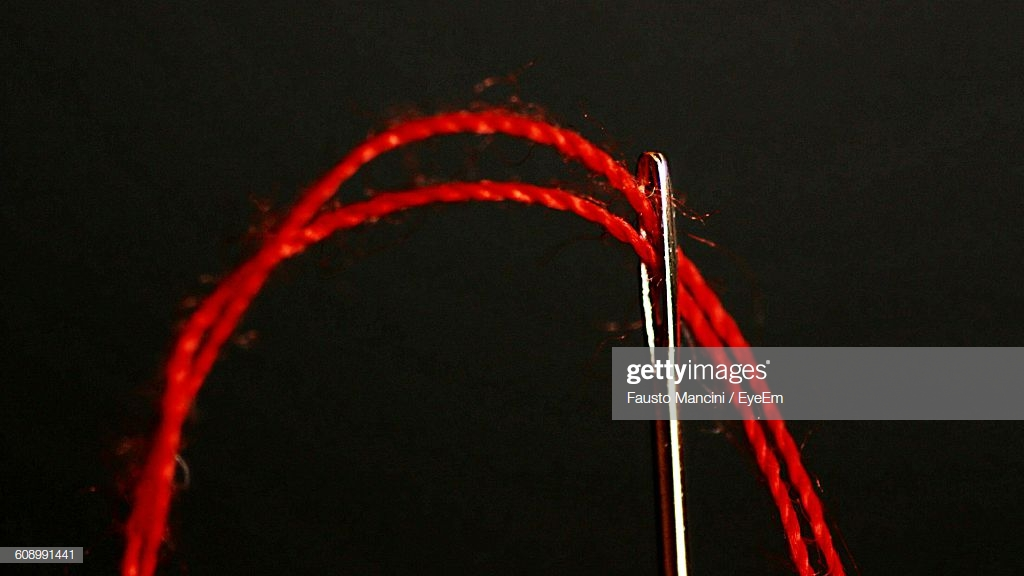 Closeup Of Red Thread Going Through Needle Against Black 1024x576