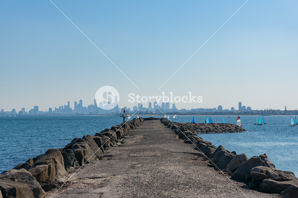 Long pier jetty with sailing boats and modern cityscape on the 1000x665