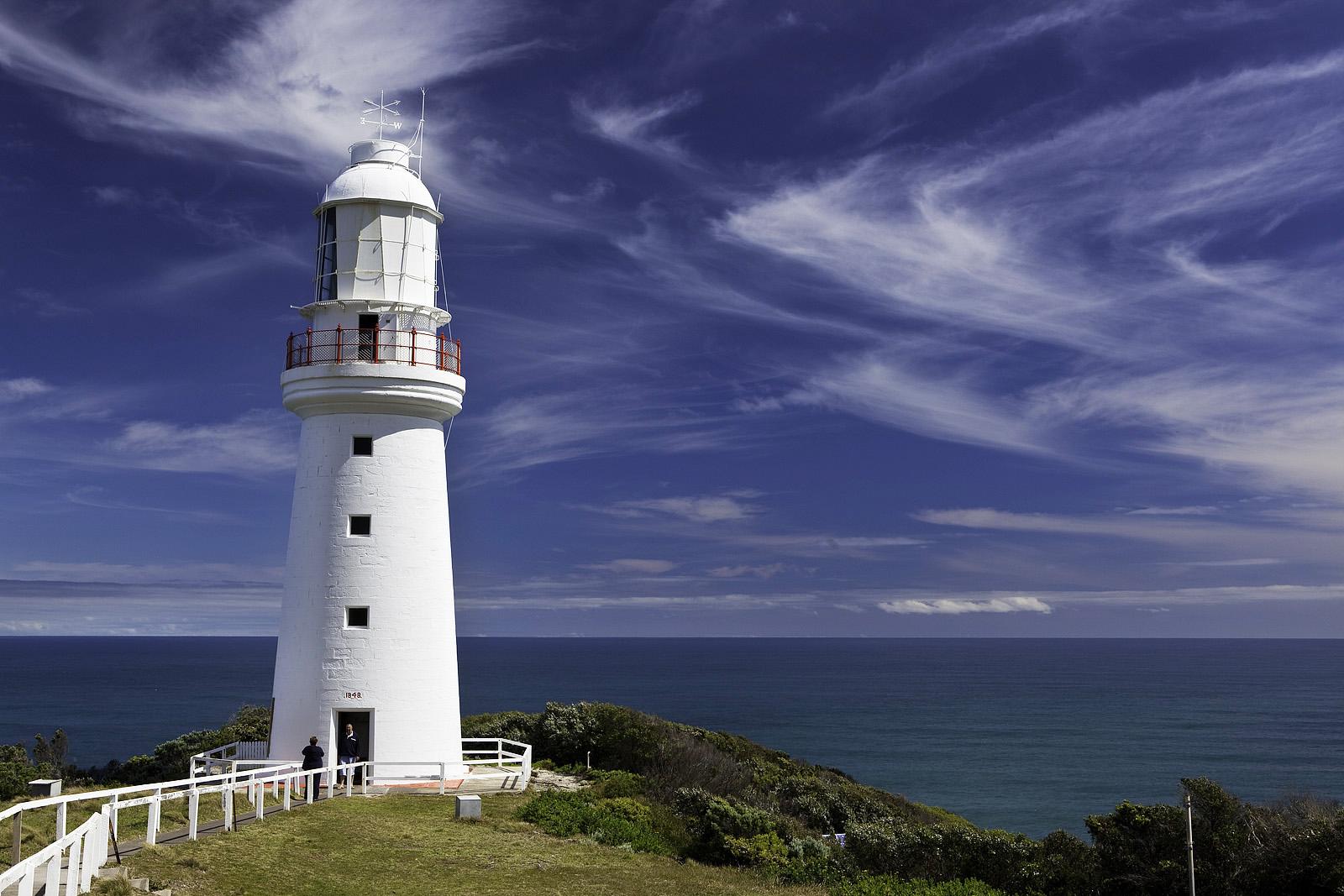 фото маяка на скале с видом в море том