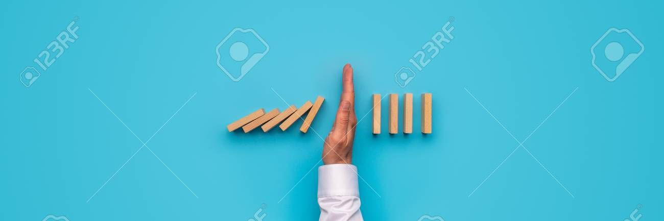 Wide View Image Of Male Hand Stopping Falling Dominos Over Blue 1300x433