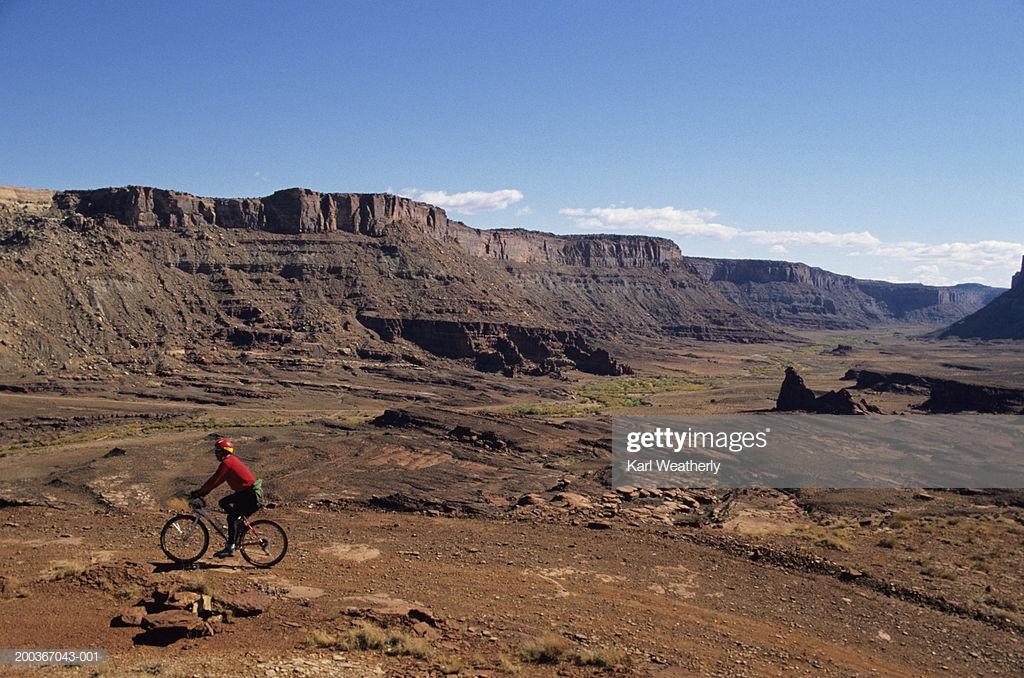 Mountain Biker On Trail Cliffs In Background Stock Photo   Getty 1024x678
