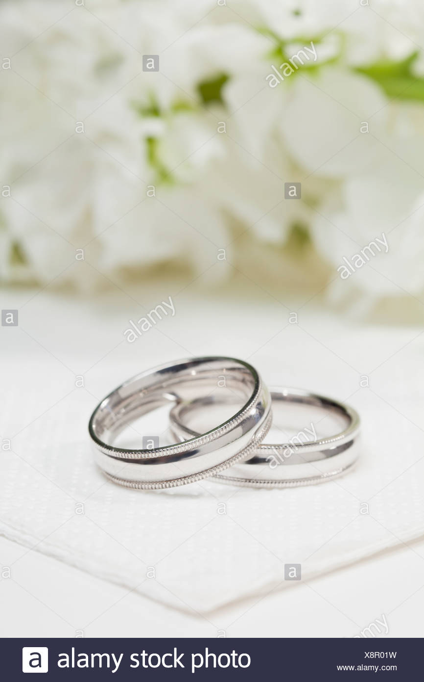Close up of wedding rings with white flowers in background Stock 866x1390