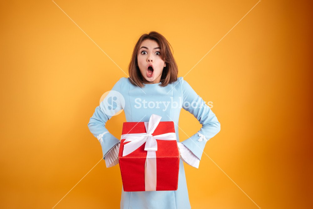 Amazed shocked young woman with opened mouth holding present box 1000x667