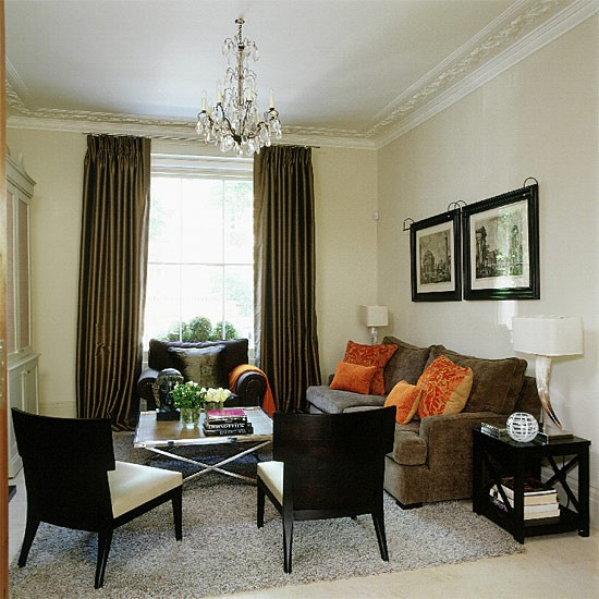 of orange help break up the brown and neutral palette in a living room 550x550