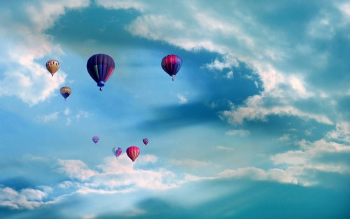 Colorful hot air balloons flying up above the blue sky 500x313