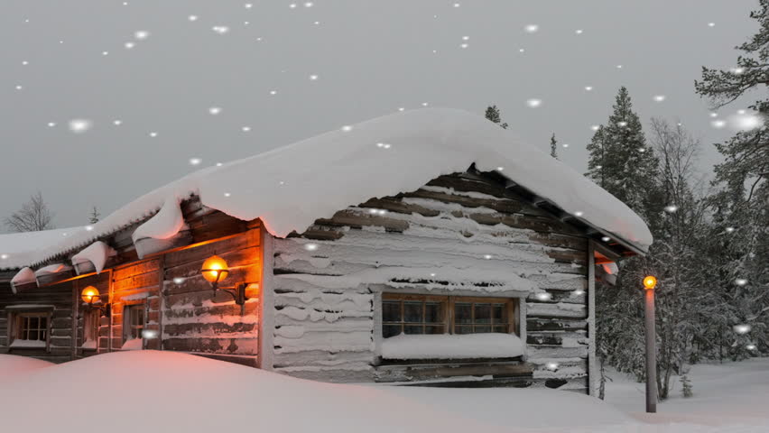 Warm welcoming snow covered timber or log home in a winter snowfall 852x480