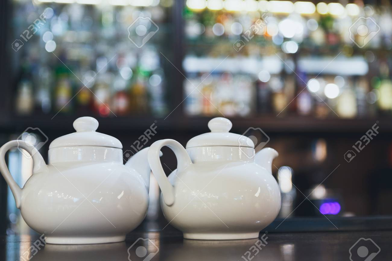 Bar Counter With Two White Teapots Blurred Alcohol Bottles 1300x866
