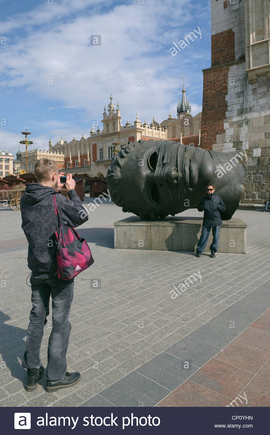 Tourist posing to picture against a background of sculpture of 863x1390