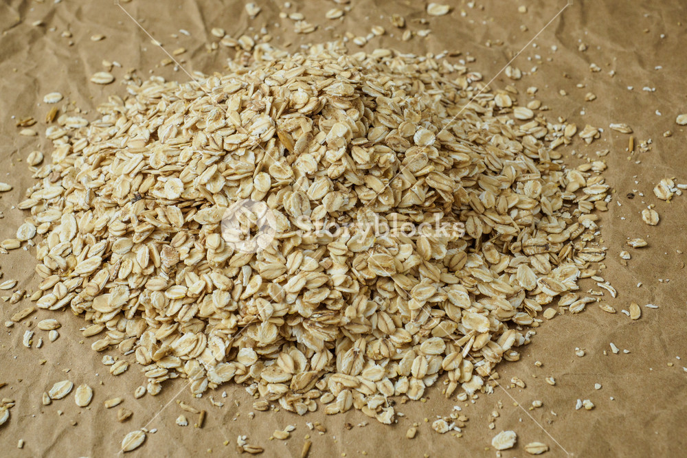 Pouring oatmeal flakes on crumpled paper background Royalty 1000x667