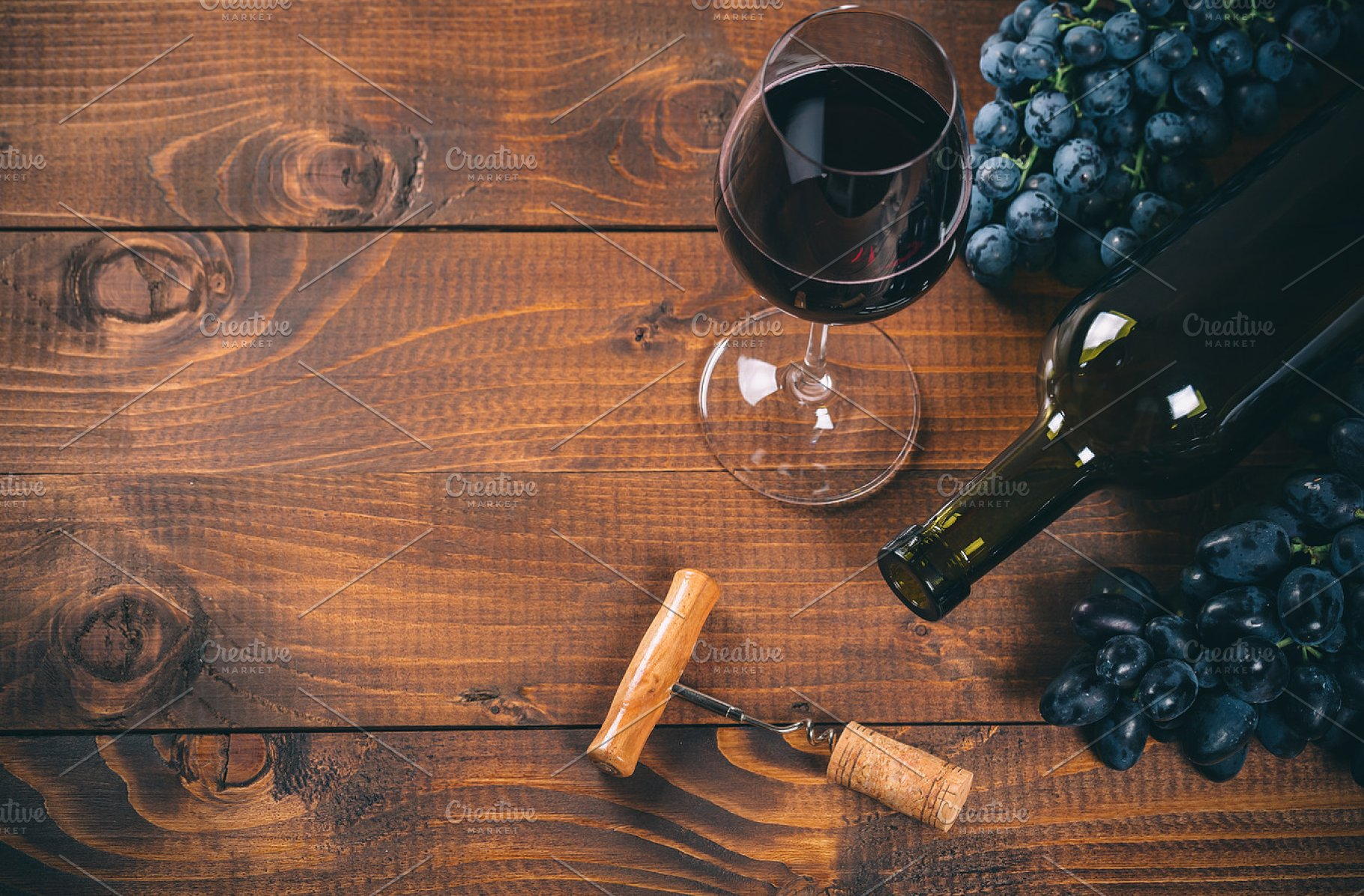 Bottle and glass of red wine grape corkscrew and cork on wooden 1820x1196