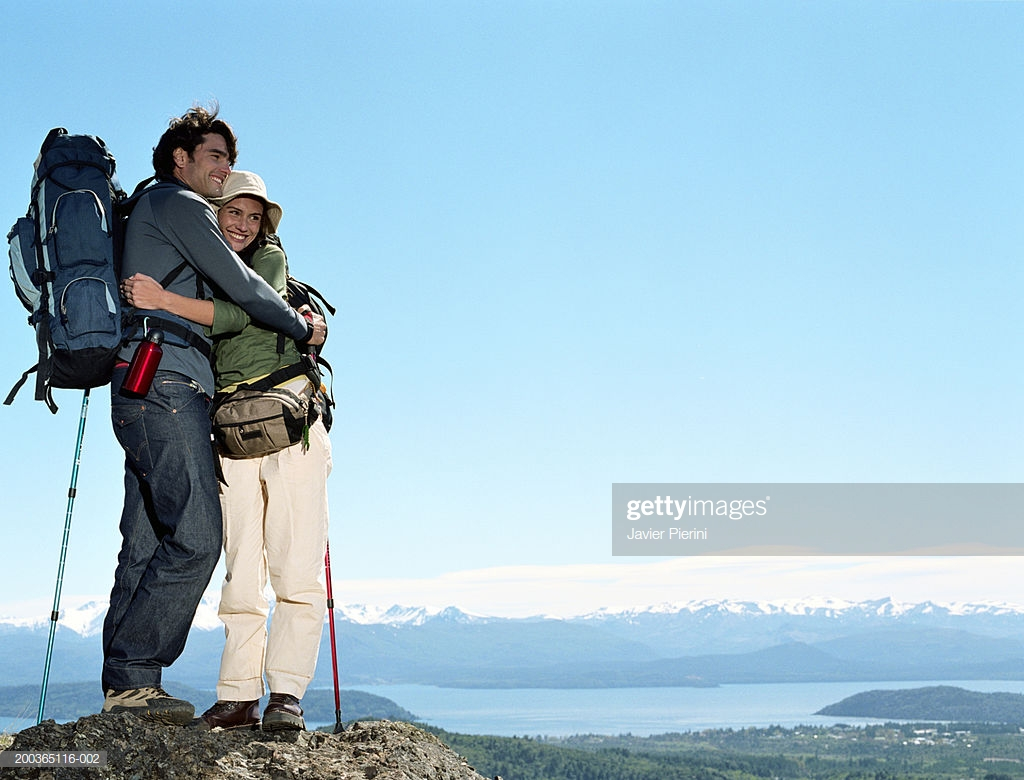 Young Couple Hiking Embracing On Mountaintop Lake In Background 1024x780