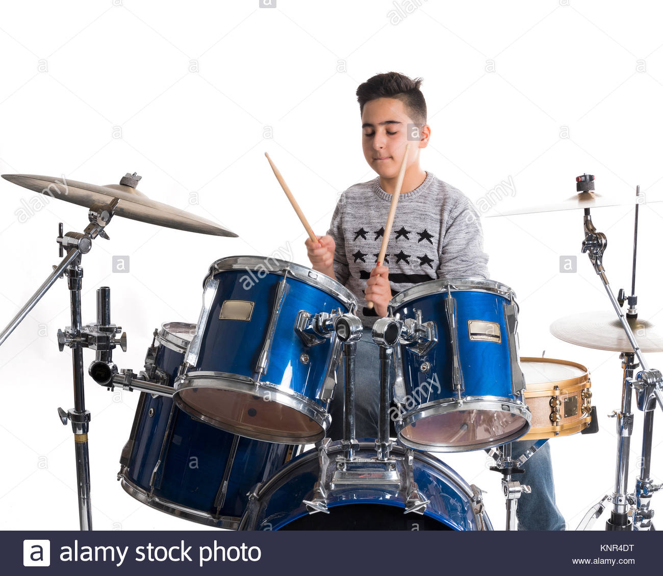 teen boy at drumset in studio against white background Stock Photo 1300x1129
