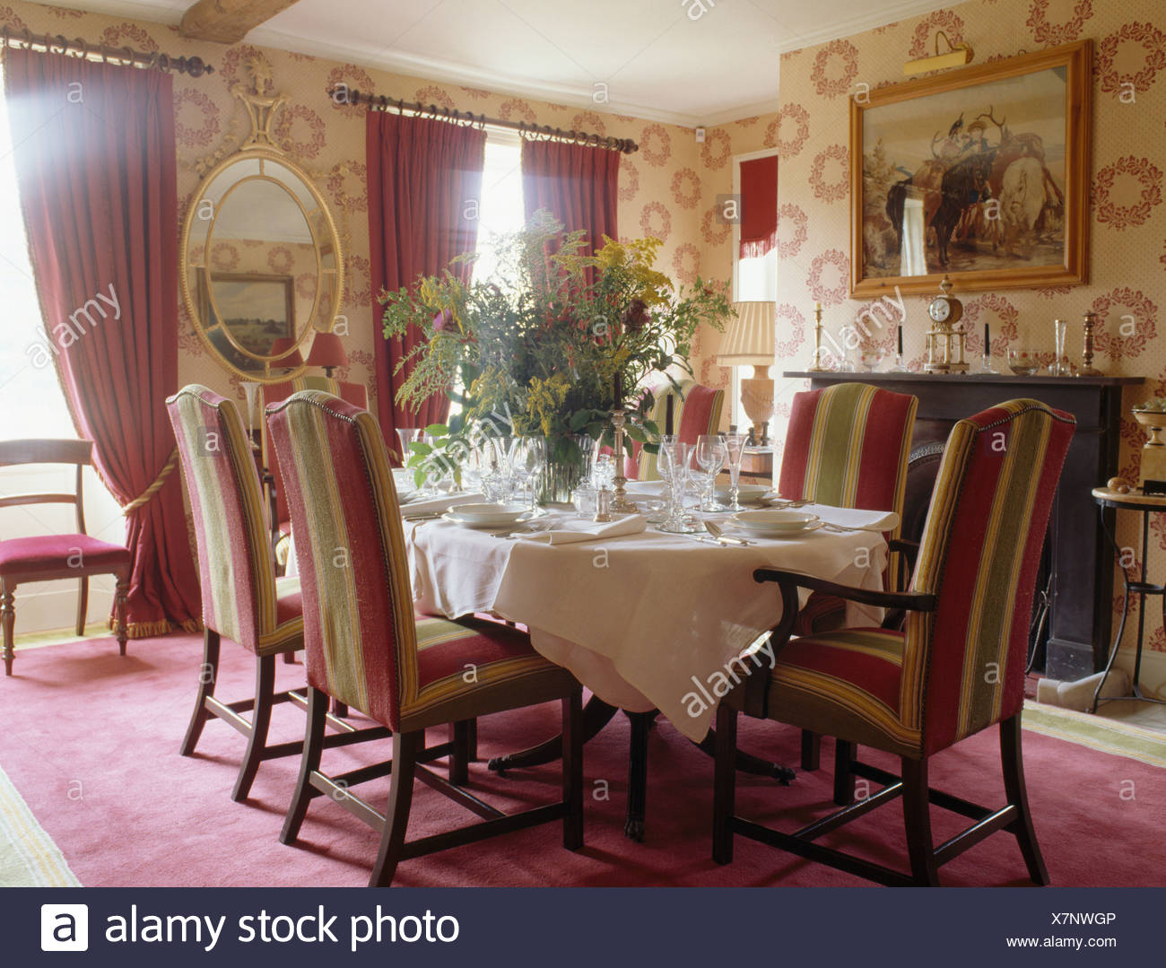 Patterned wallpaper and striped upholstered chairs in traditional 1300x1079