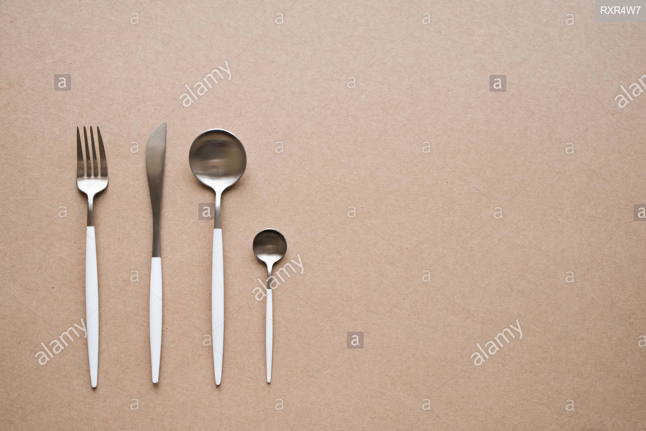 Set of stylish white and chrome cutlery on beige background top 1300x868