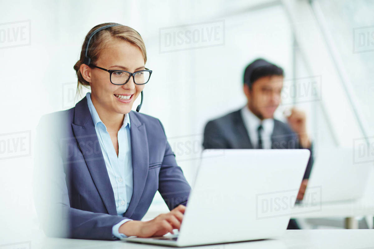 Pretty operator consulting clients online with colleague on 1200x800