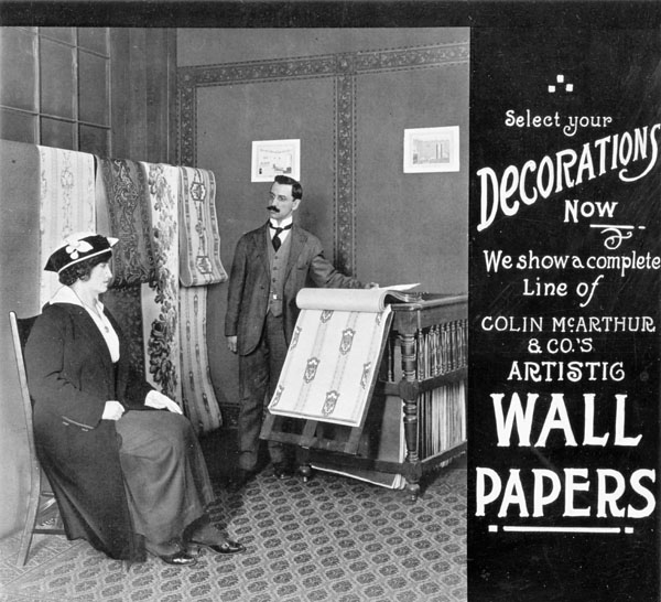 Photograph of a salesman in a wallpaper store showing samples to a 600x546