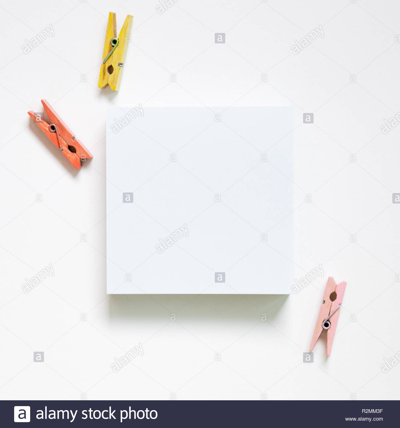 Empty memo paper sticky notes and wooden clothespins on white 1300x1390