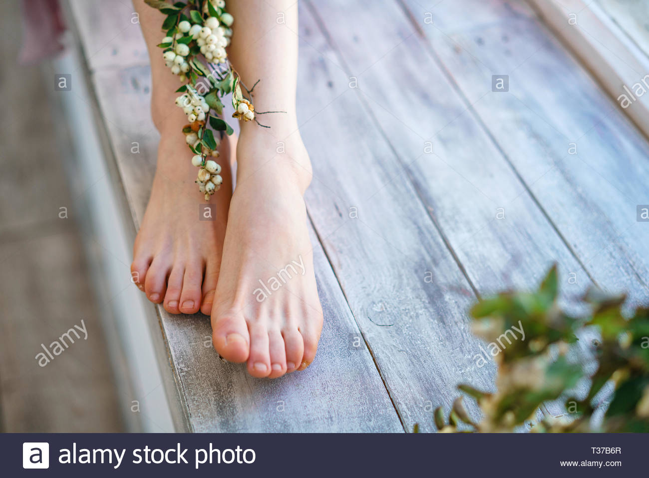 beautiful womens feet with flowers on wooden background foot 1300x957