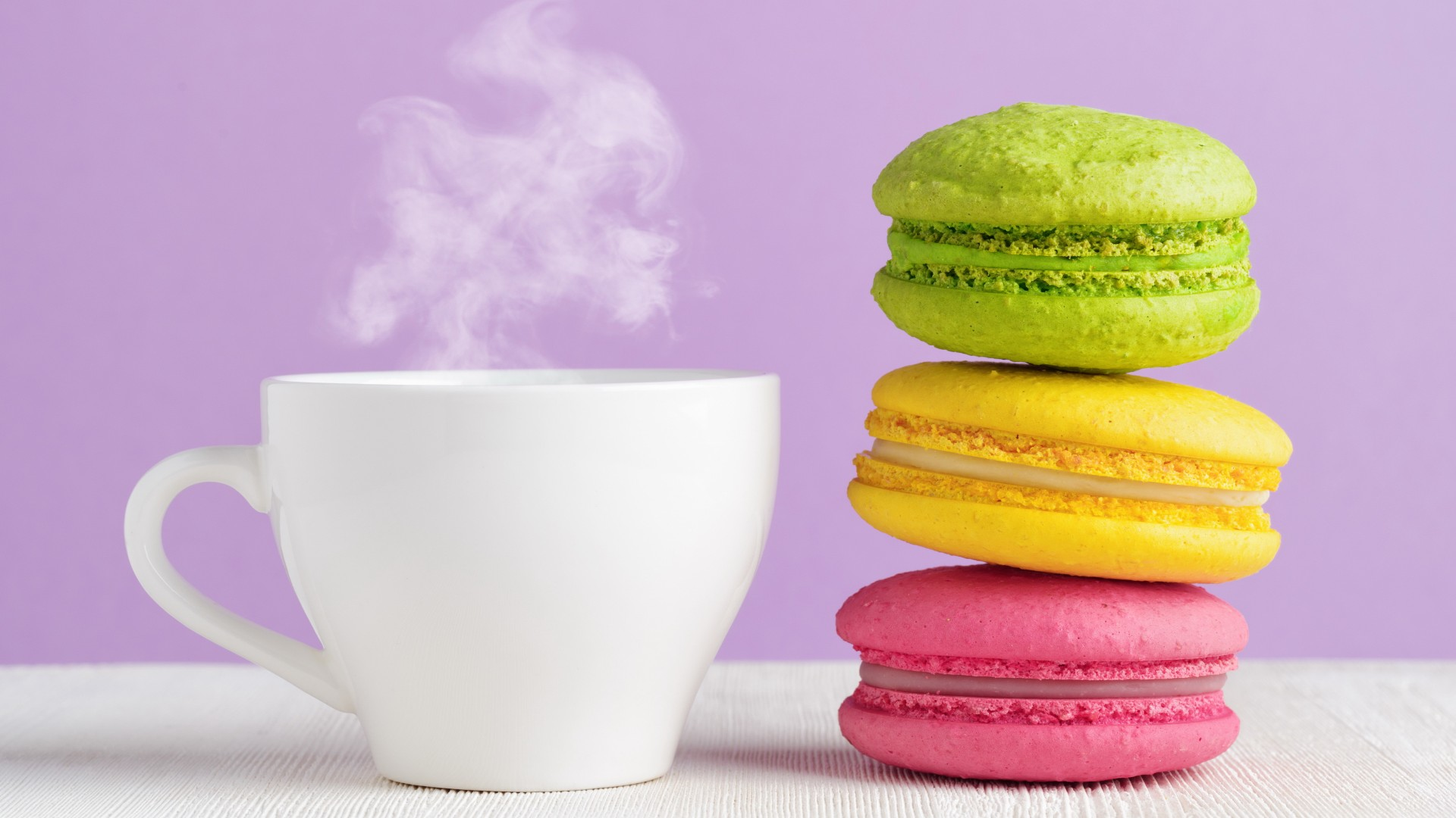 Steaming cup of coffee and colorful macaroons wallpaper 1920x1080