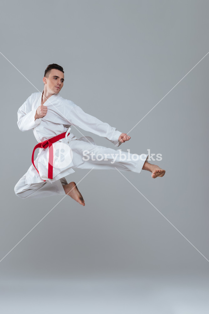 Photo of sportsman in kimono practice in karate while jumping 667x1000