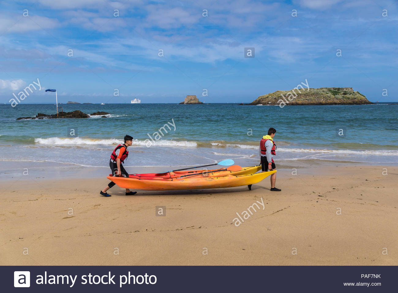 St Malo France Two young people carrying a Canoe In the 1300x956