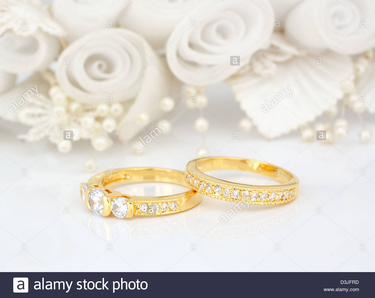 Gold wedding rings on flowers background Stock Photo 53882625   Alamy 1300x1035
