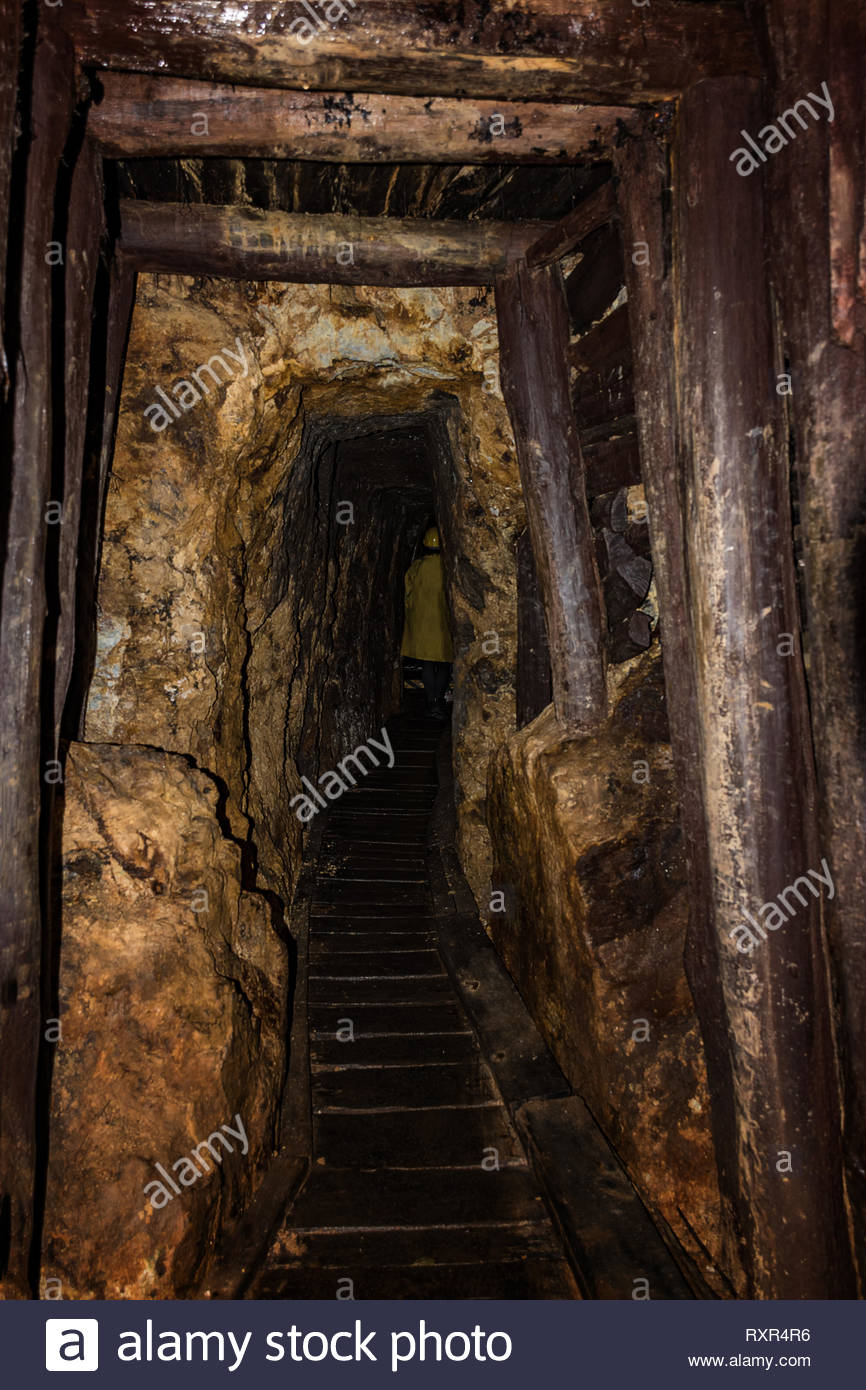 Old mine shaft with wooden timbering and person dressed in a 866x1390