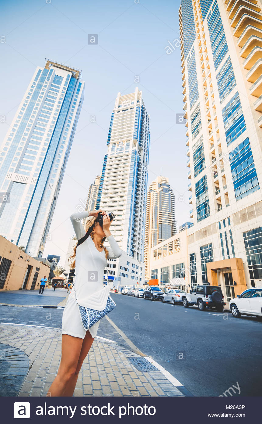 Young girl taking photo of skyscrapers background Attractive girl 861x1390