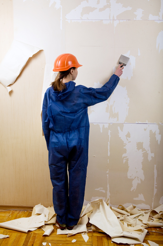Woman worker removes old wallpaper 333x500