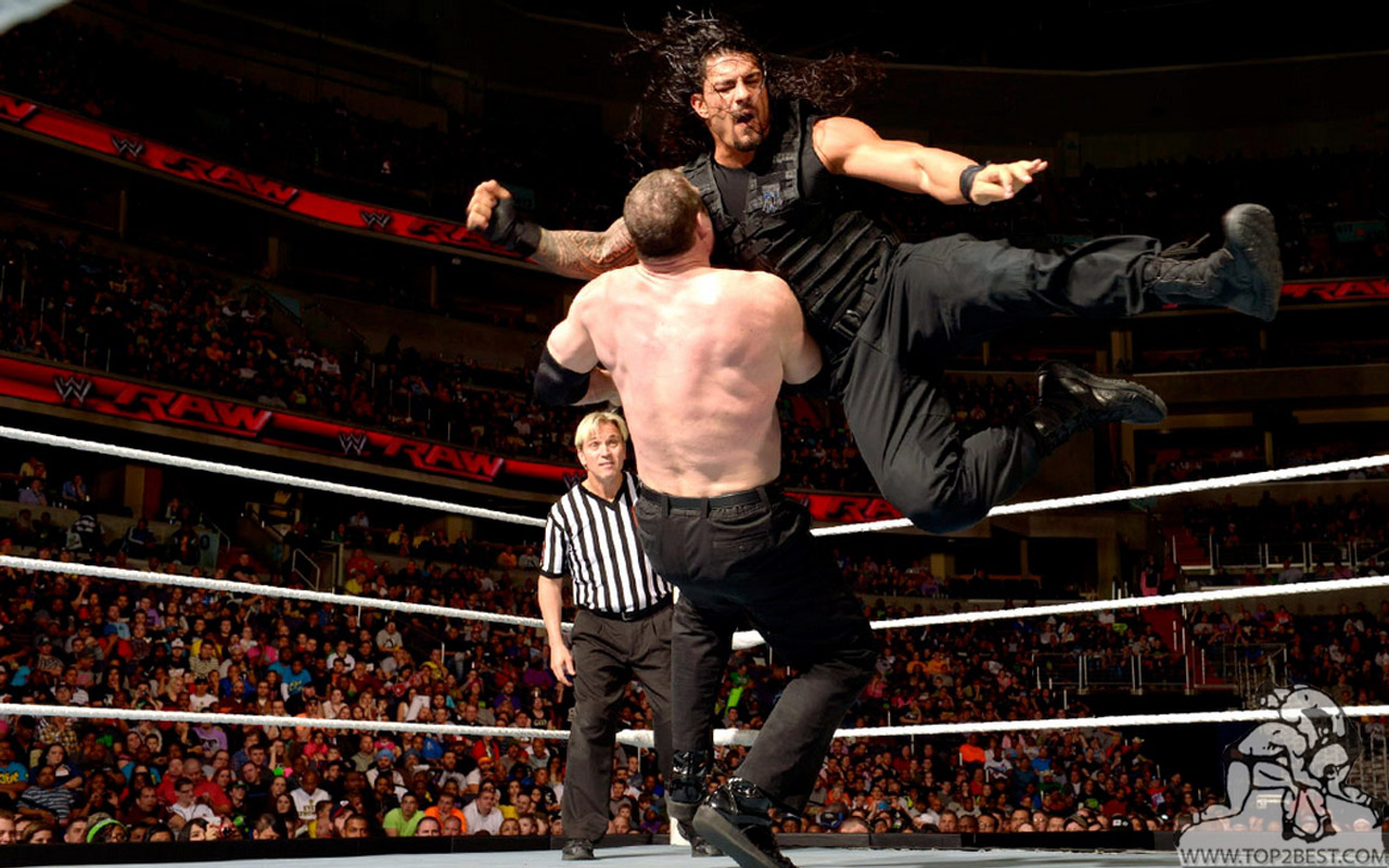 this wallpaper shows reigns flying in the air and punching the kane on ...