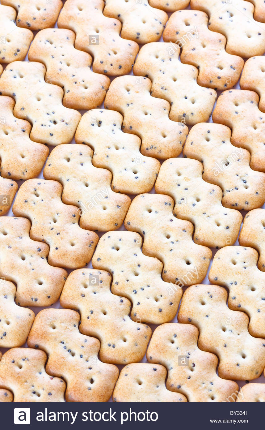 Small shaped browned crisp biscuits as tile background Stock Photo 858x1390