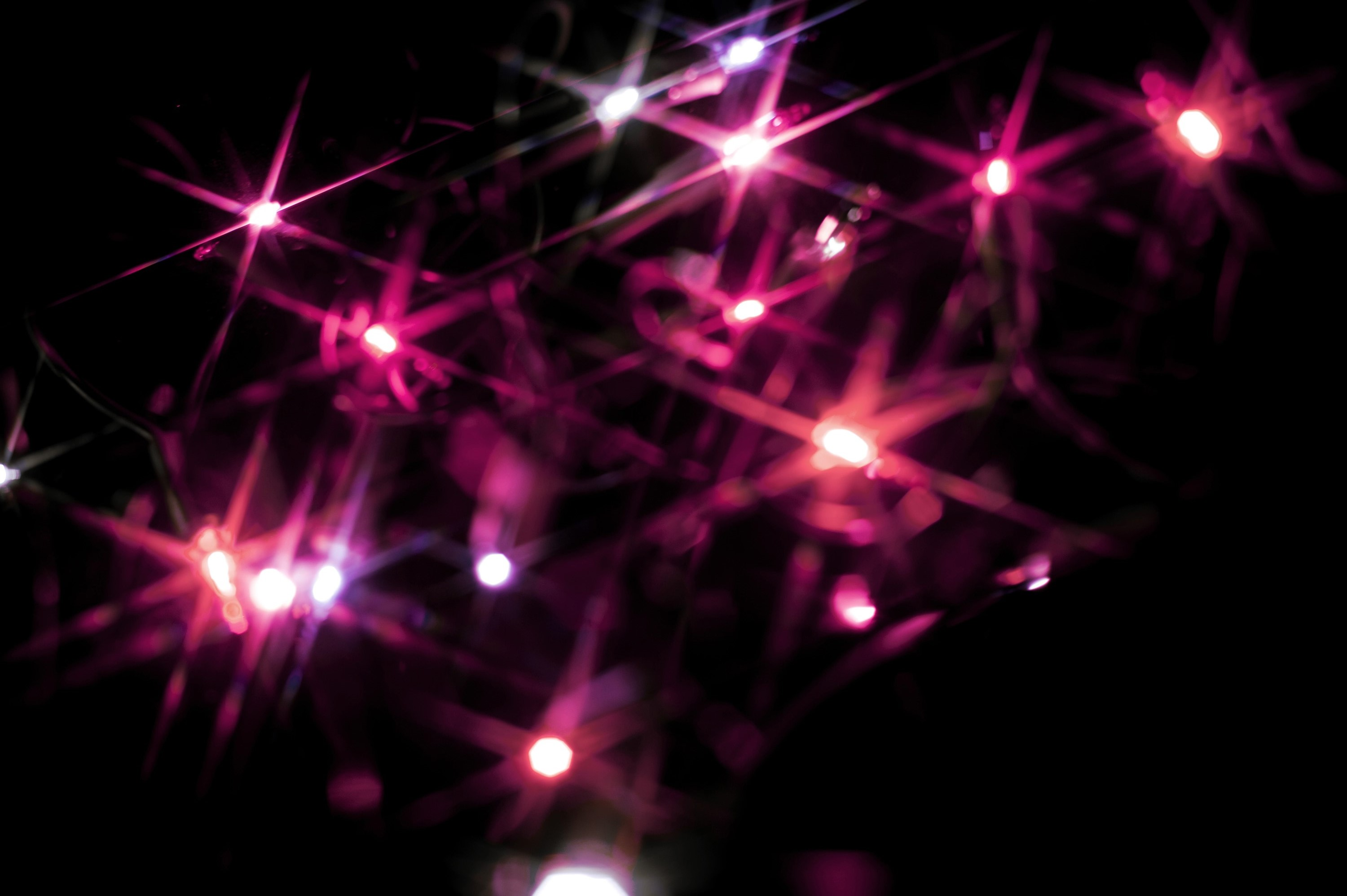 Photo of Christmas background of pink starburst lights 3000x1996