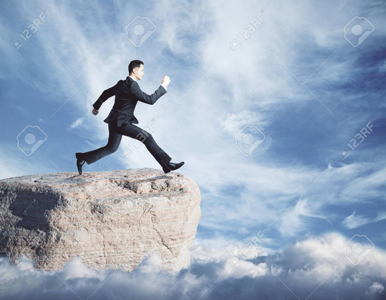 Side View Of Young Businessman Jumping Off Cliff On Sky Background 1300x1011