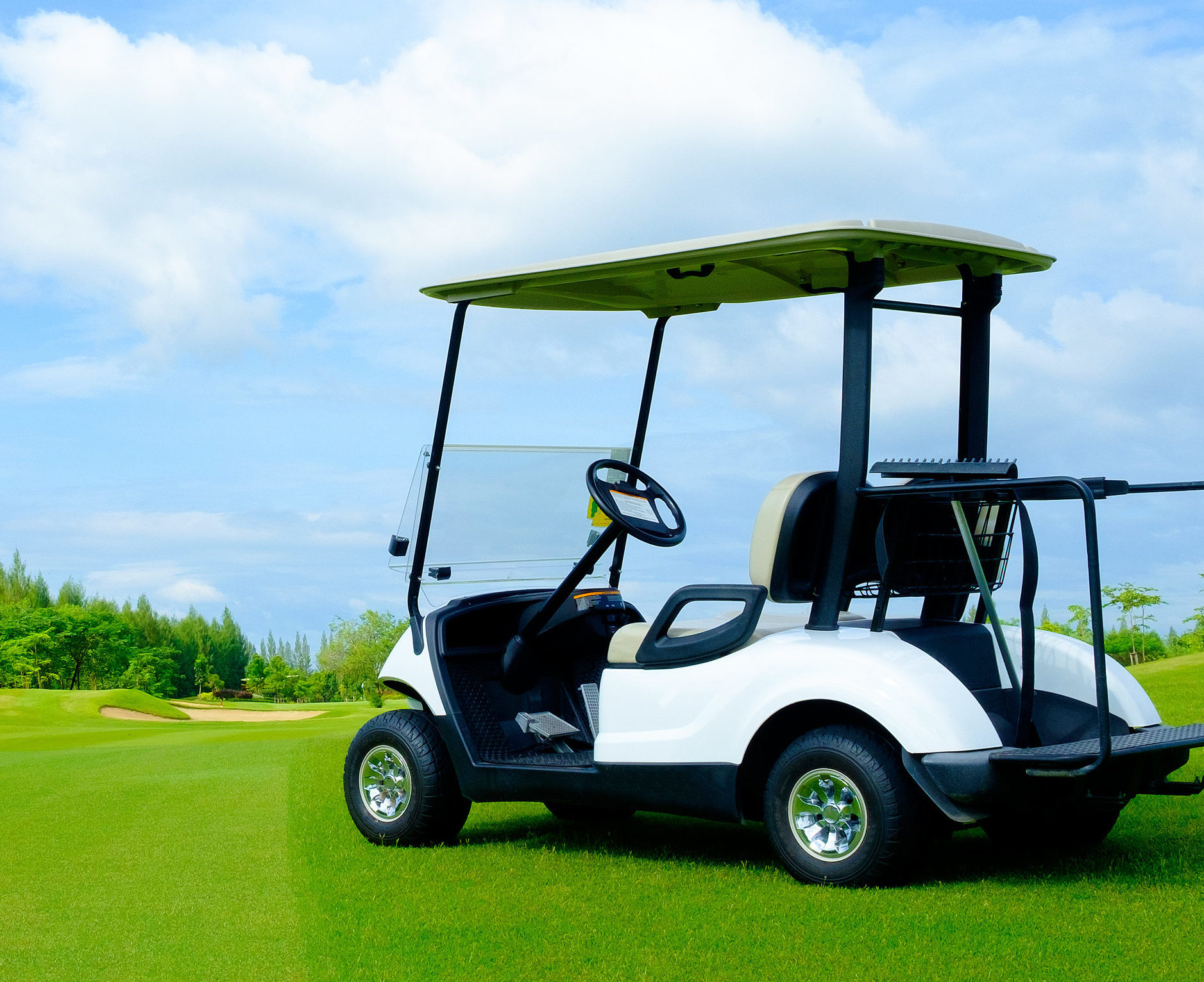 golf cart on green lawn with blue sky and cloud for background 1877x1532