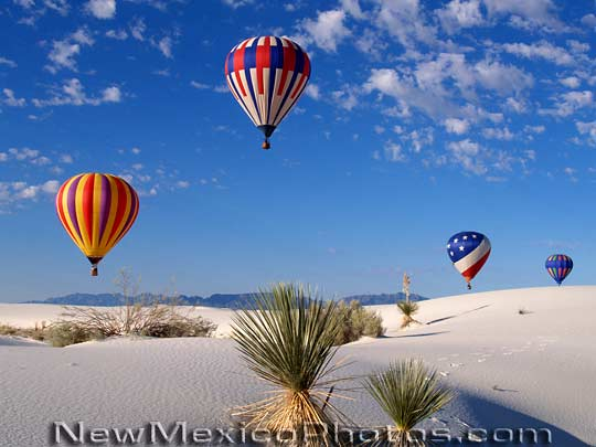 Hot air balloons hover high in the sky above White Sands National 540x405