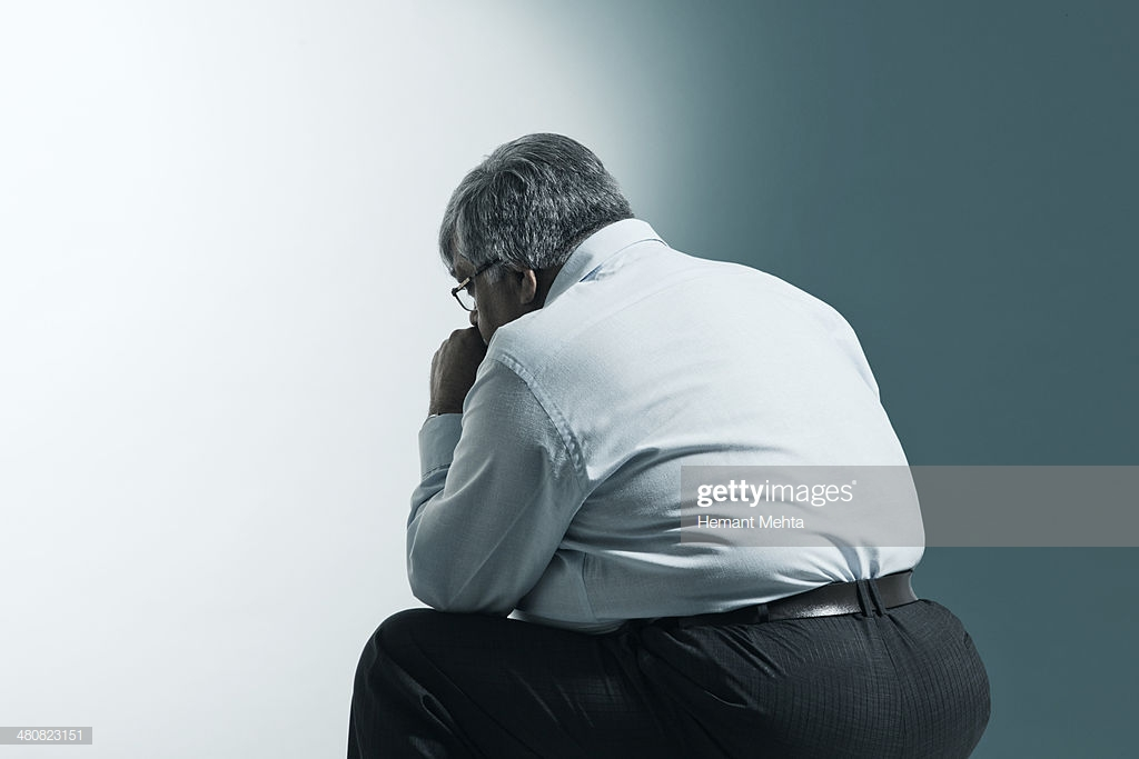 Rear View Of Overweight Mature Man Sitting Against Blue Background 1024x683