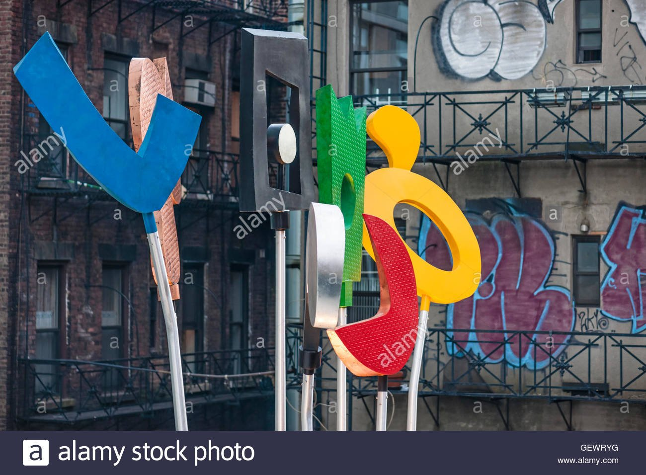Detail of colourful sculptural building sign with graffiti in 1300x956