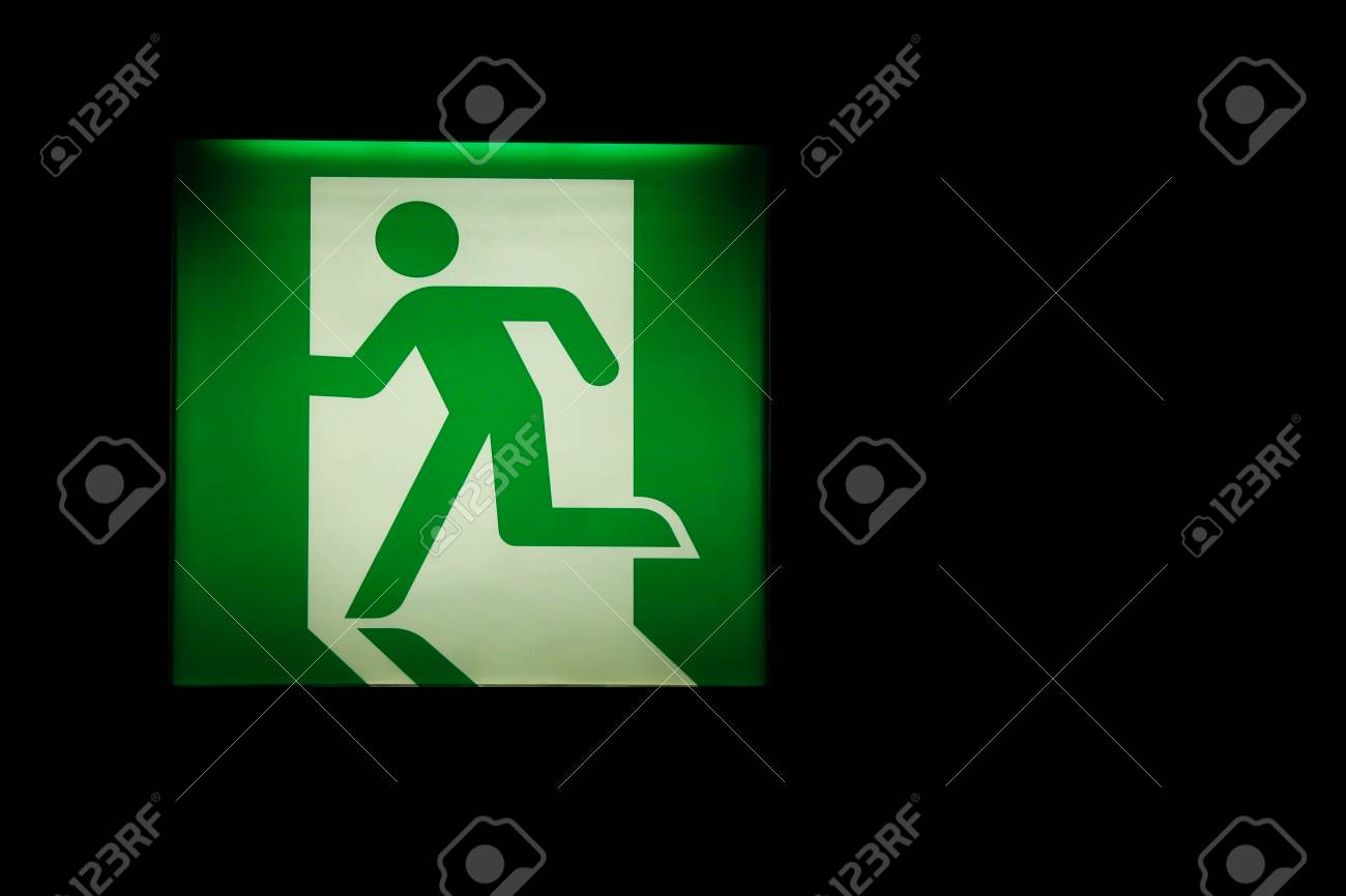Emergency Exit Way Sign Board On The Dark Room Wall Background 1300x866