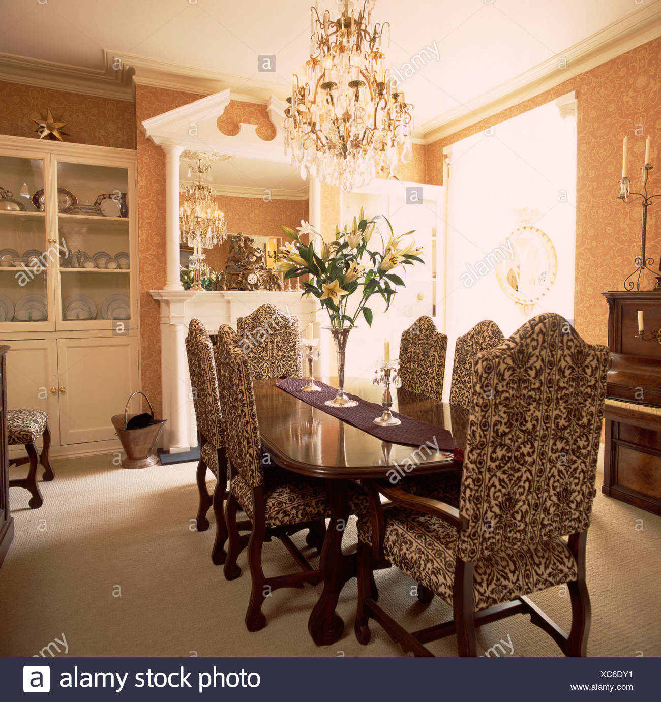Chandelier above tapestry upholstered chairs and mahogany table in 1300x1381