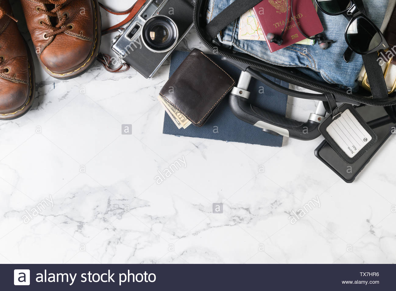 prepare suitcase accessories and travel items background on marble 1300x956