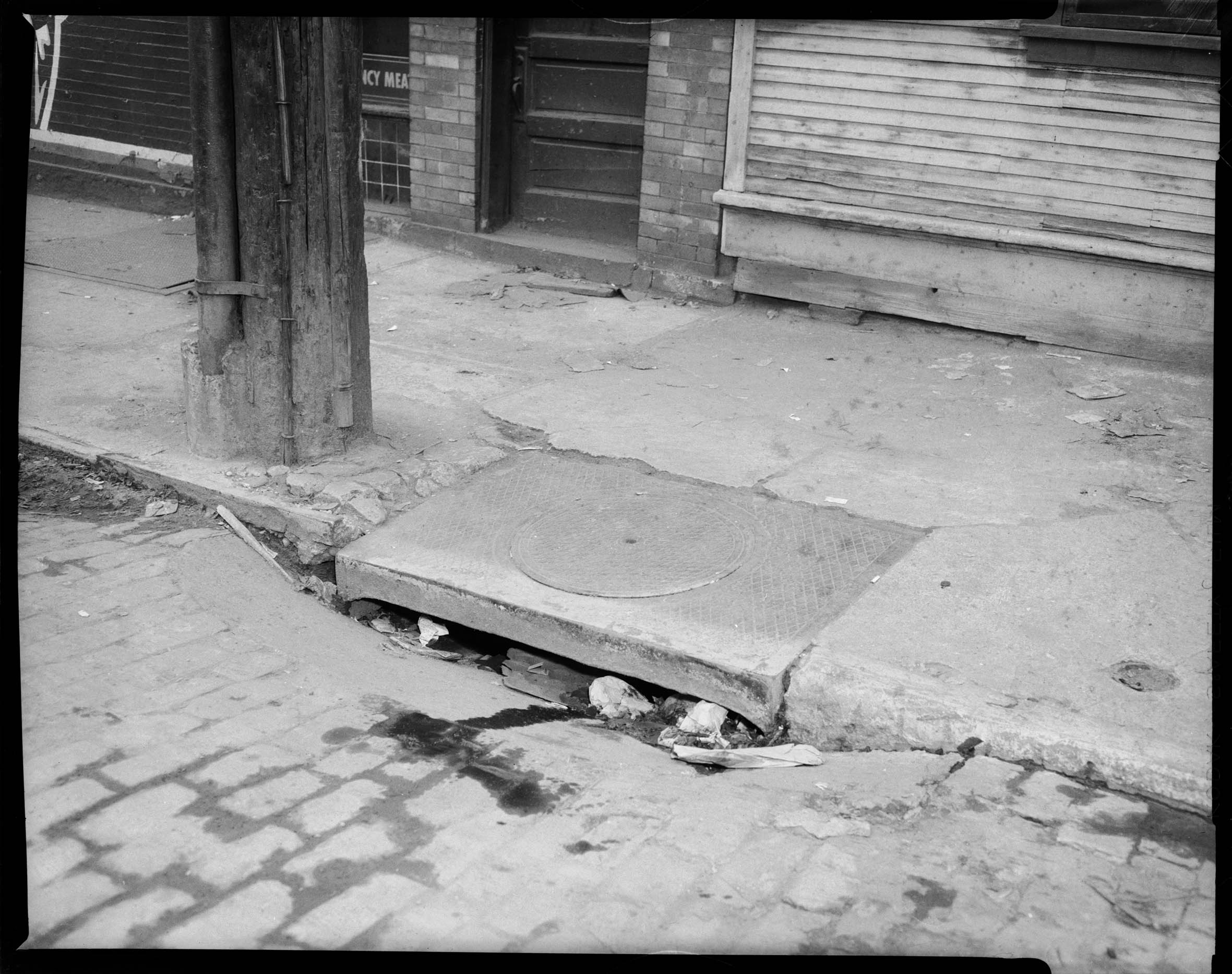Sidewalk with patched pavement and clogged sewer drain with store 2361x1867