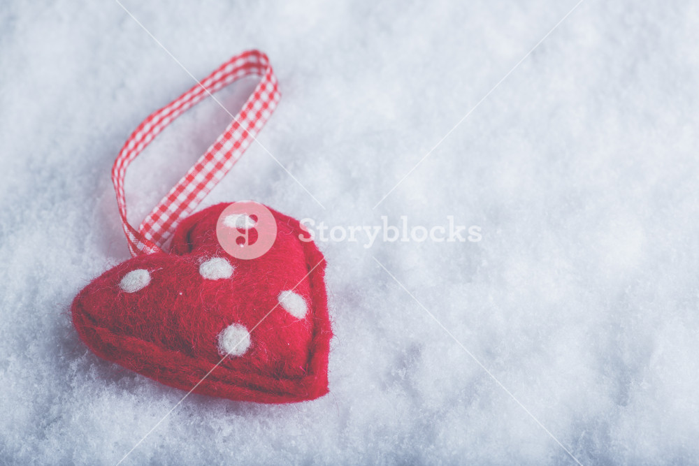 Red toy suave heart on a frosty white snow winter background 1000x667