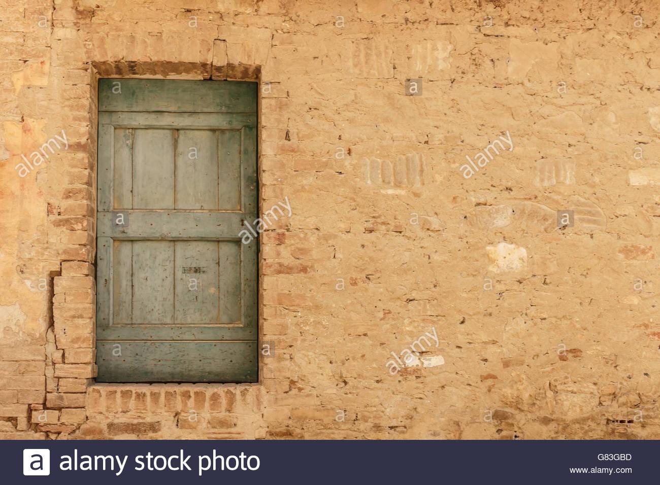 Rustic wooden door in colour color in random stonework 1300x956
