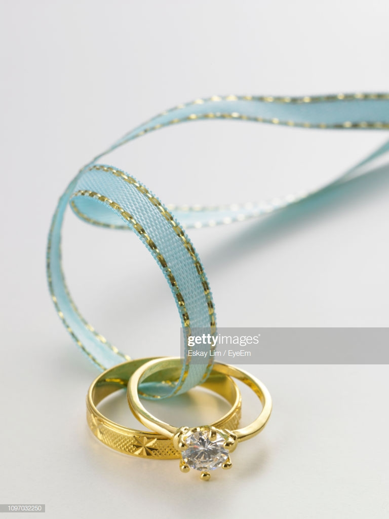 Closeup Of Wedding Rings In Blue Ribbon On Gray Background Stock 768x1024