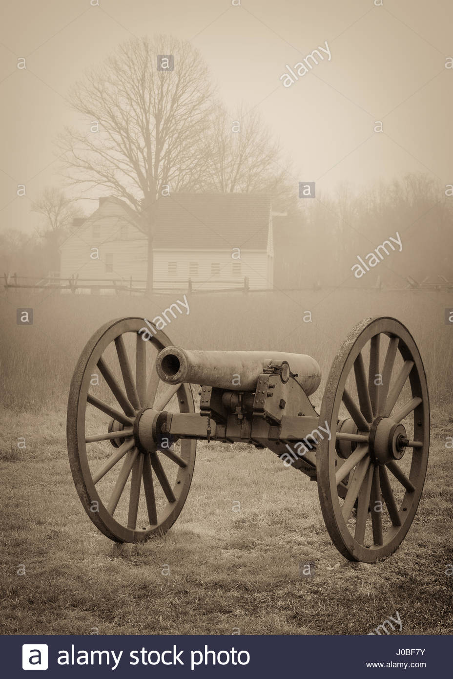 A civil war cannon with a farm house in the background at Cold 928x1390
