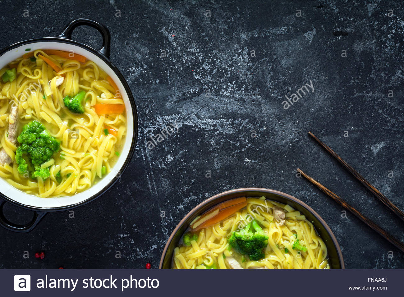 Asian egg noodle soup with vegetables and pork on dark slate Stock 1300x956