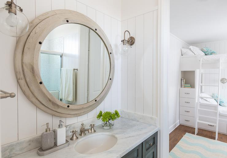 Kids cottage bathroom features vertical shiplap walls lined with a 740x515
